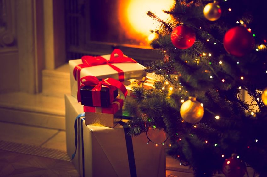 Toned photo of Christmas tree and gift boxes against burning fir